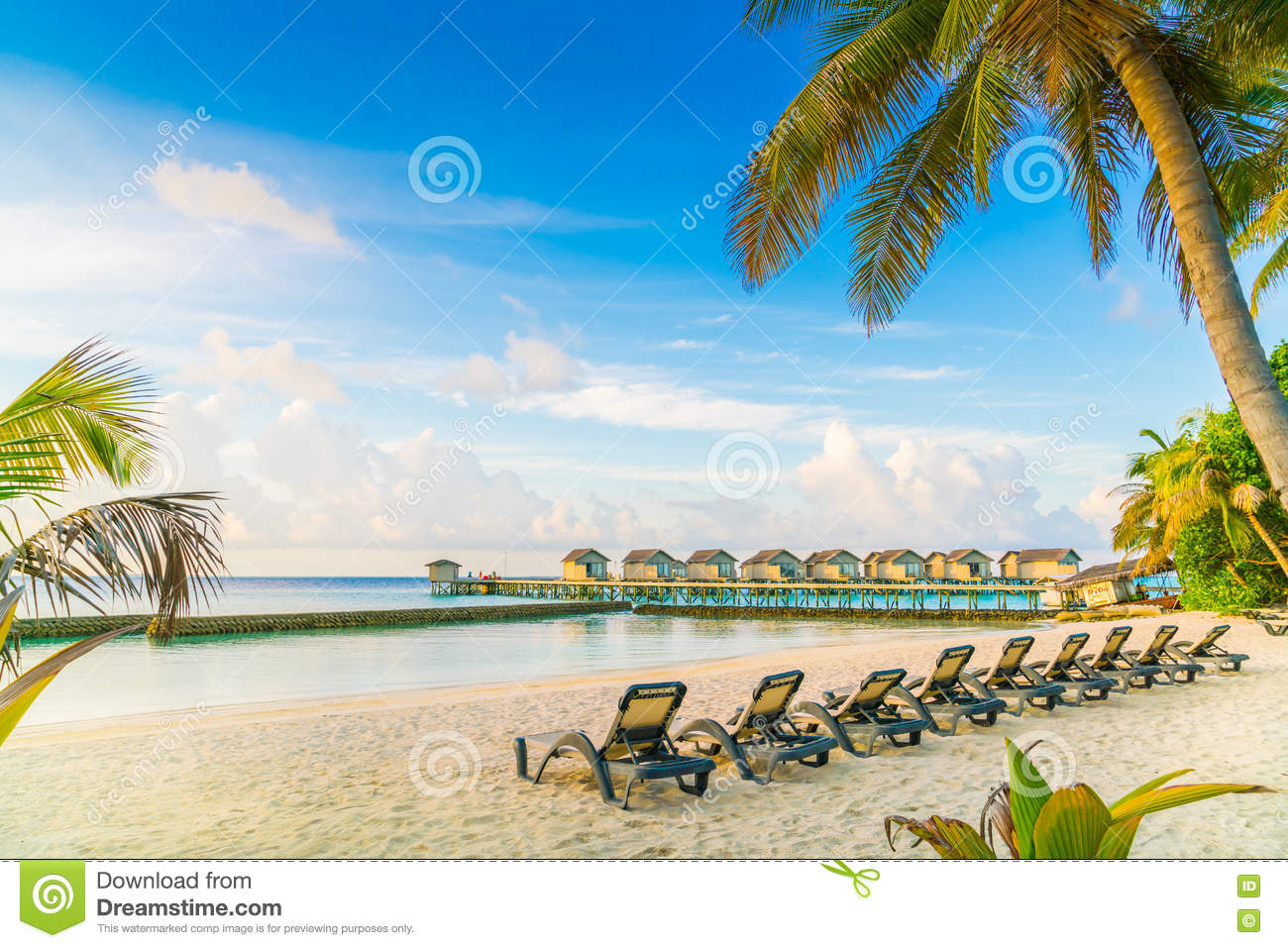 Beach chairs sunrise - Beach Chairs In Maldives Island With Water Villas At The Sunrise Stock Photo