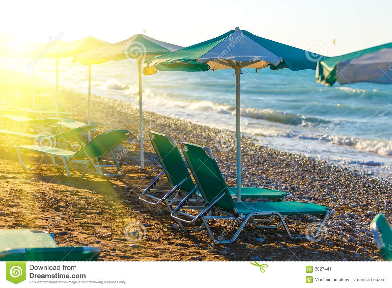 Beach chairs and umbrella on the shore of a pebbly beach Greece Rhodes with sun flare twilight time