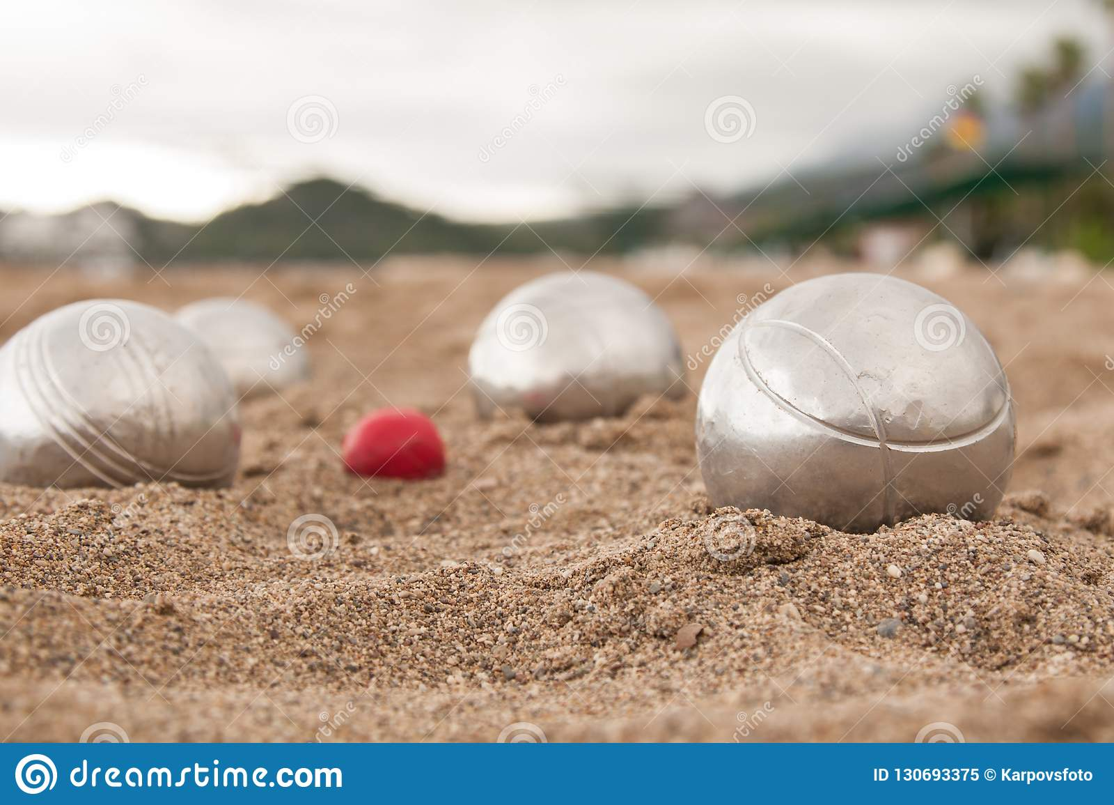 Brilliant silver balls for a bocha on the sand.