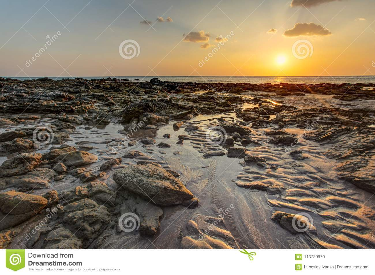 Beach in golden sunset light during low tide showing sand format