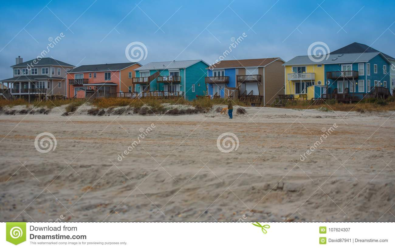 Beach houses with sand and grass and storm clouds