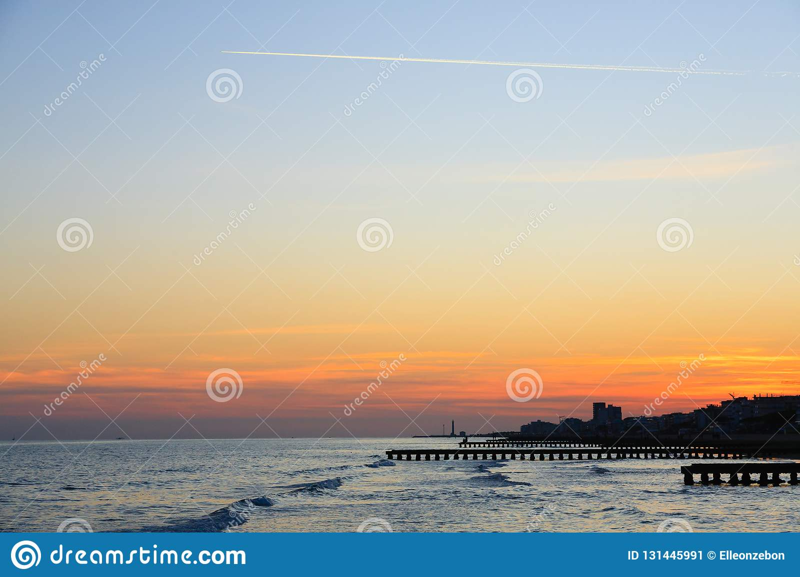 Beach landscape at dawn. Piers perspective view with people. Jesolo beach view