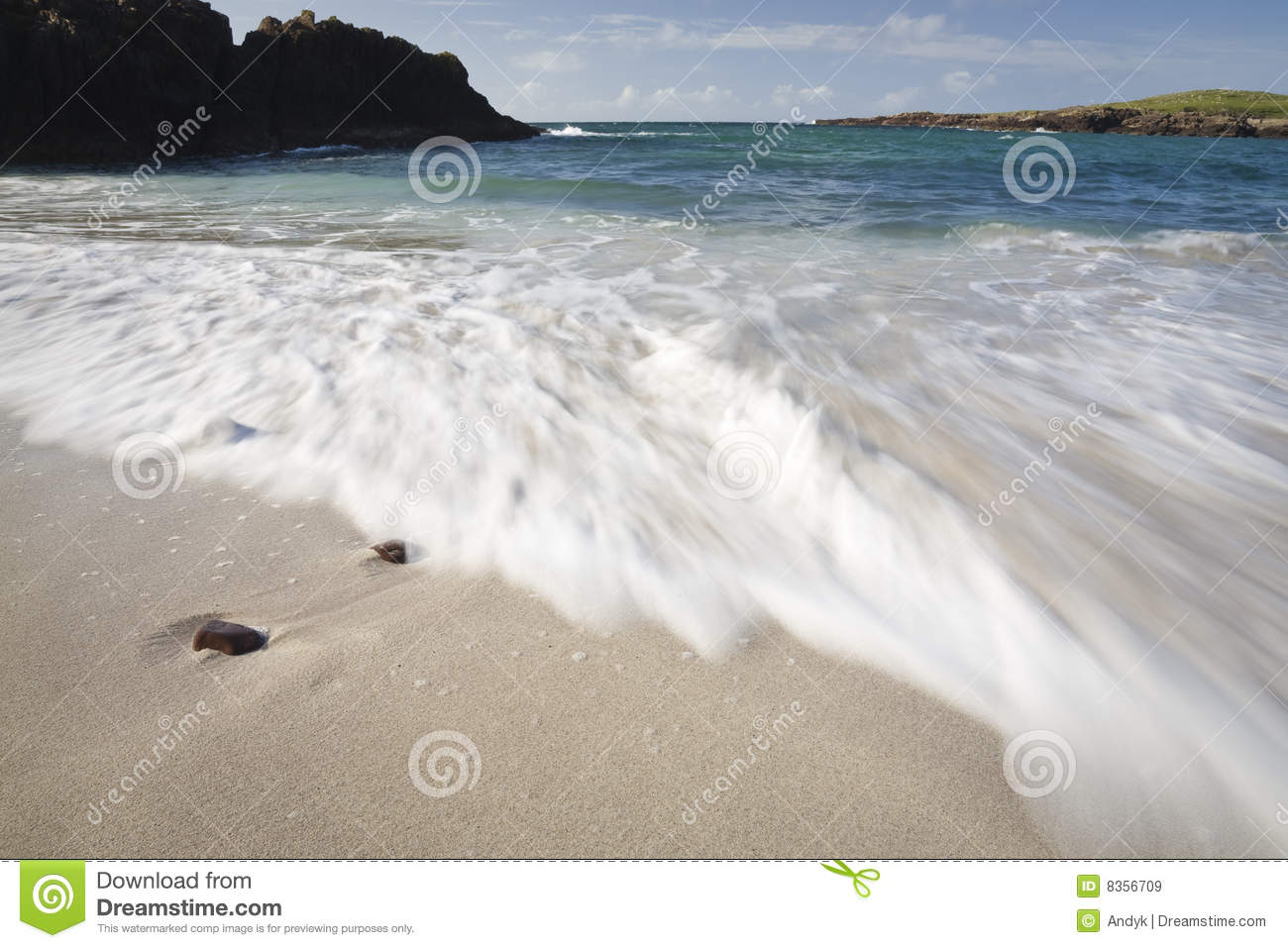 Beach line with blue sky, clouds and breaking wave