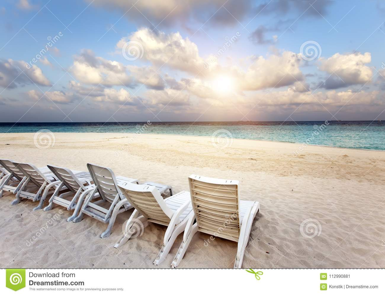 Beach lounge chairs on a beautiful tropical sand beach with cloudy blue sky. Maldives