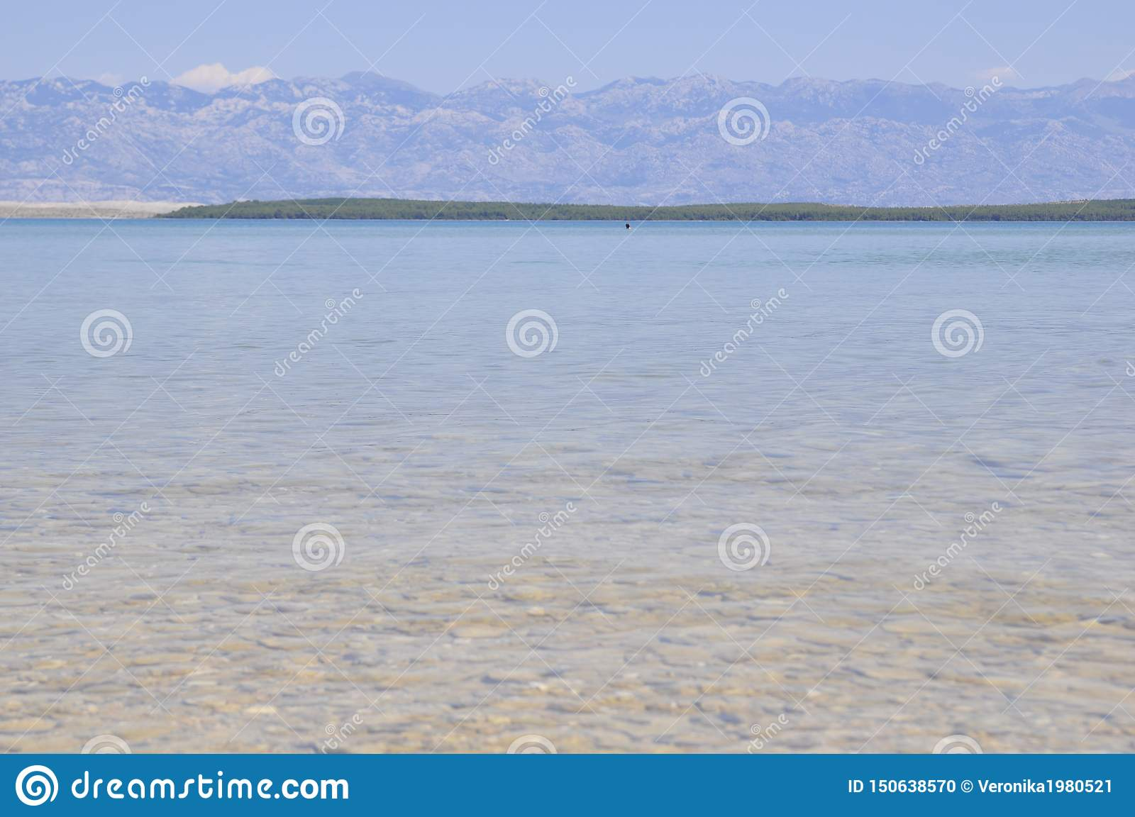 Beach. Sea. The mountains. Clear water. Stones under water.