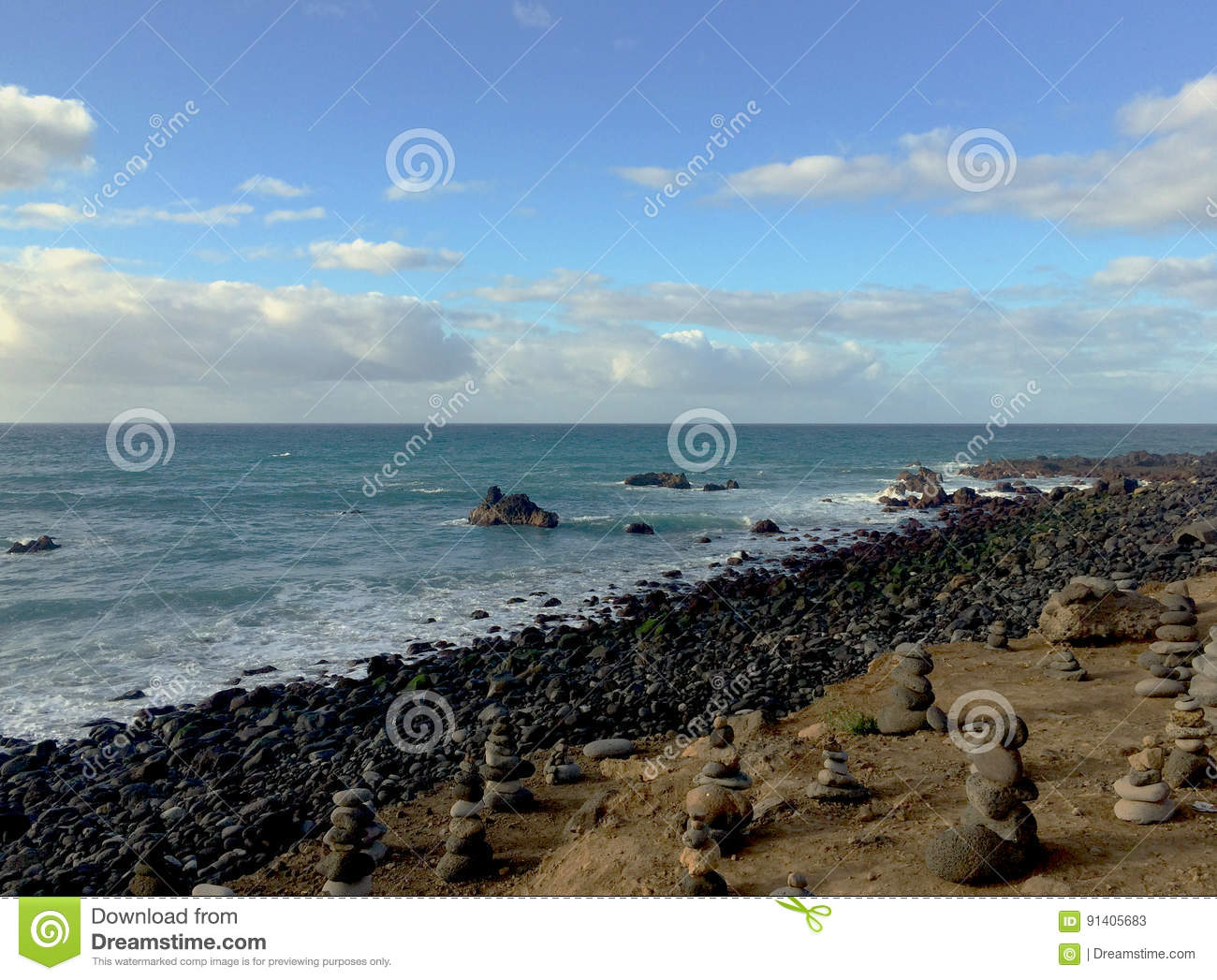 Beach shore full of monoliths made with flat stones with sea background