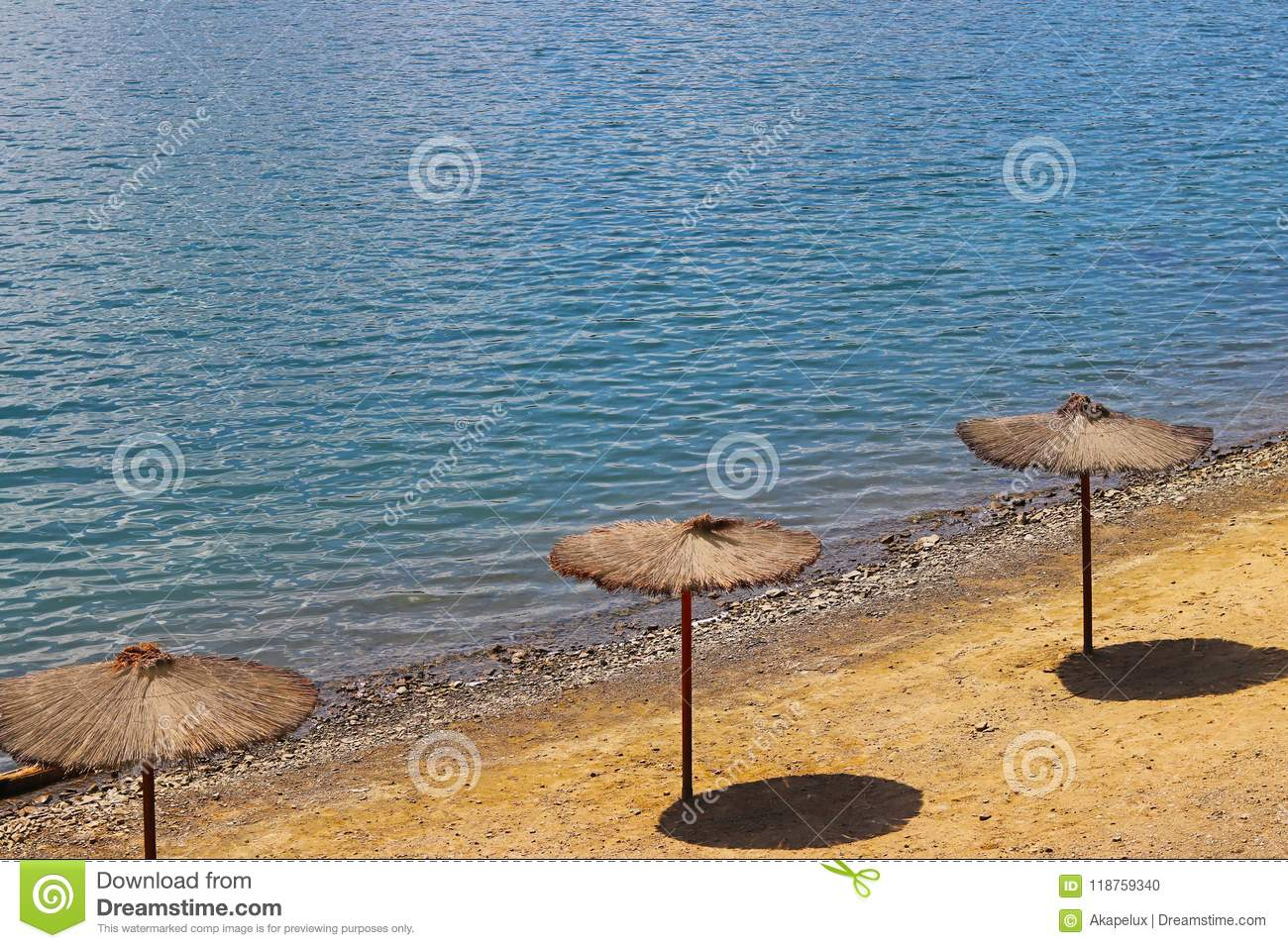 Beach with umbrellas from a creeper. Quality and comfort of rest at the water. Protection from sunlight. Rest on the beach and pon