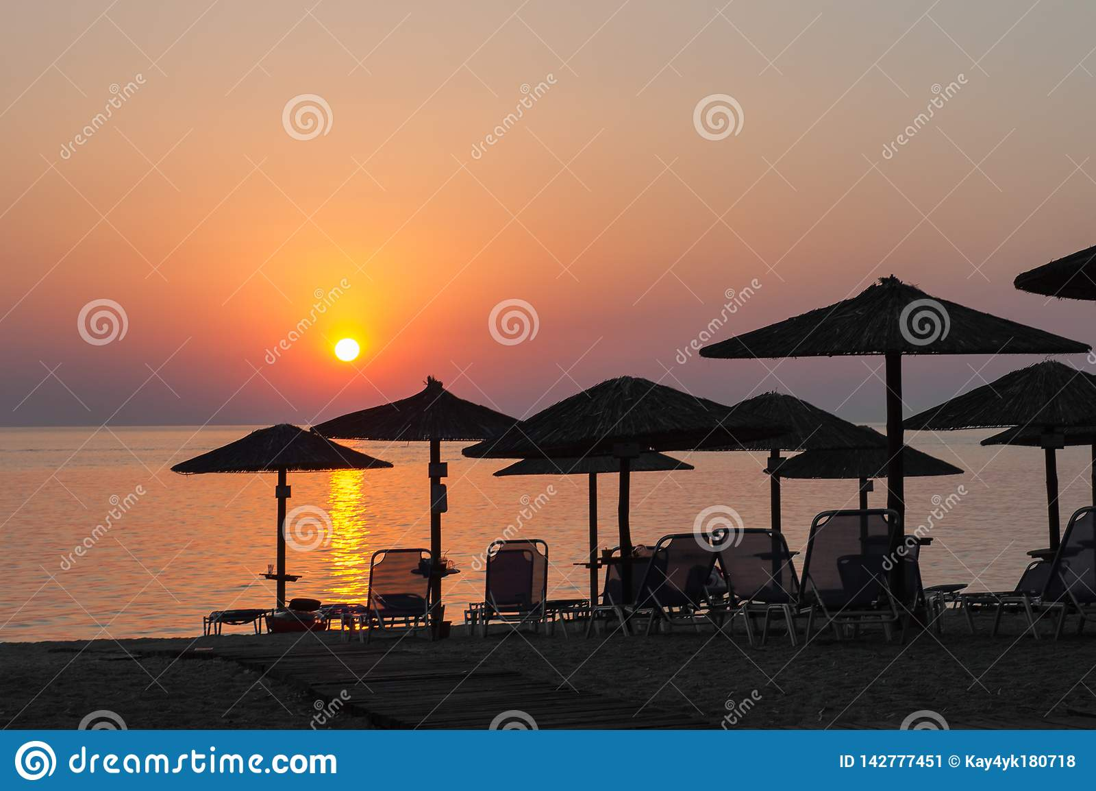 Beach umbrellas at sunset, with sunbeds, hot sunset on the beach