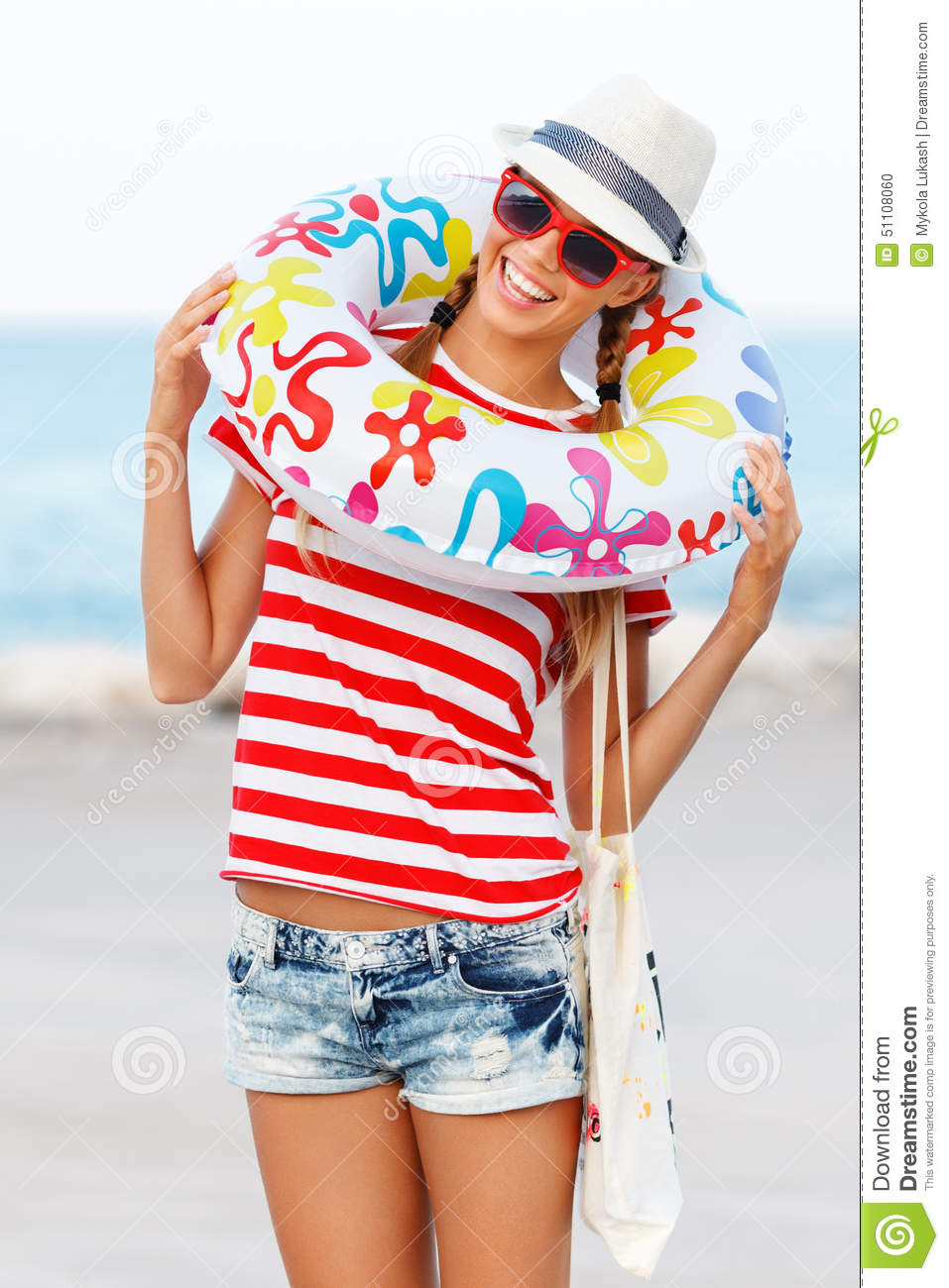 Beach woman happy and colorful wearing sunglasses and beach hat having summer fun during travel holidays vacation