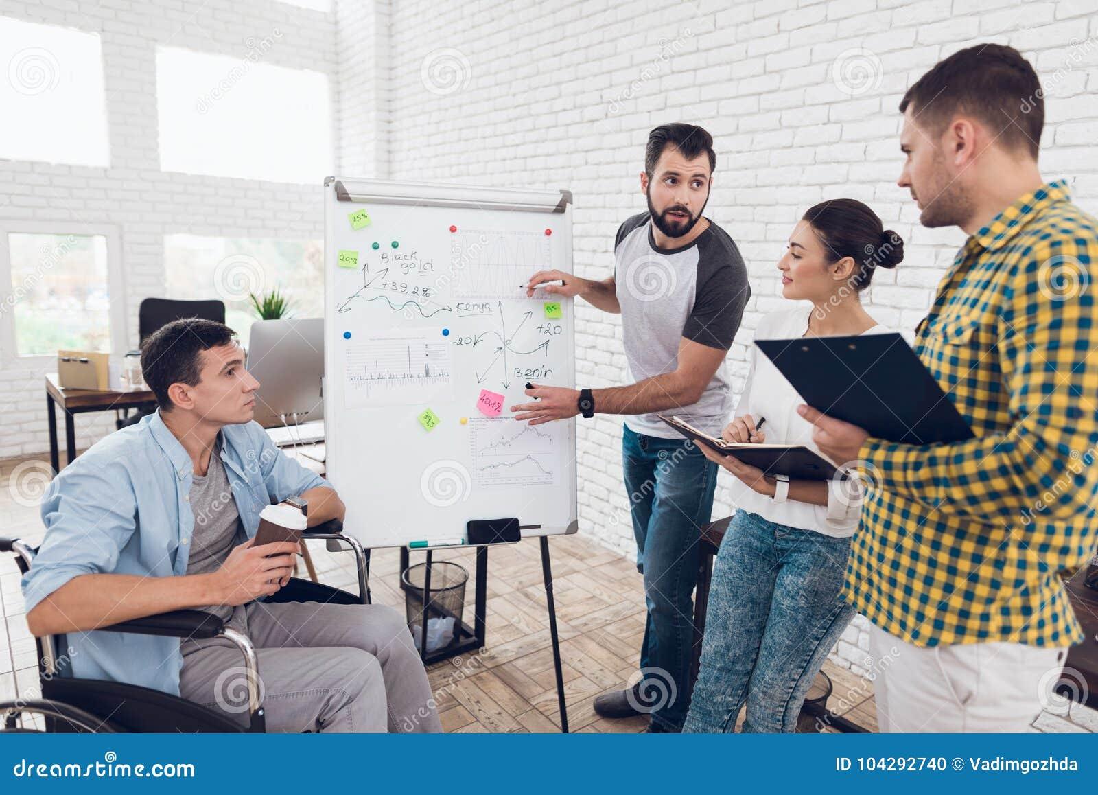 Beambten en mens in een rolstoel die bedrijfsogenblikken bespreken terwijl het werken in een modern bureau