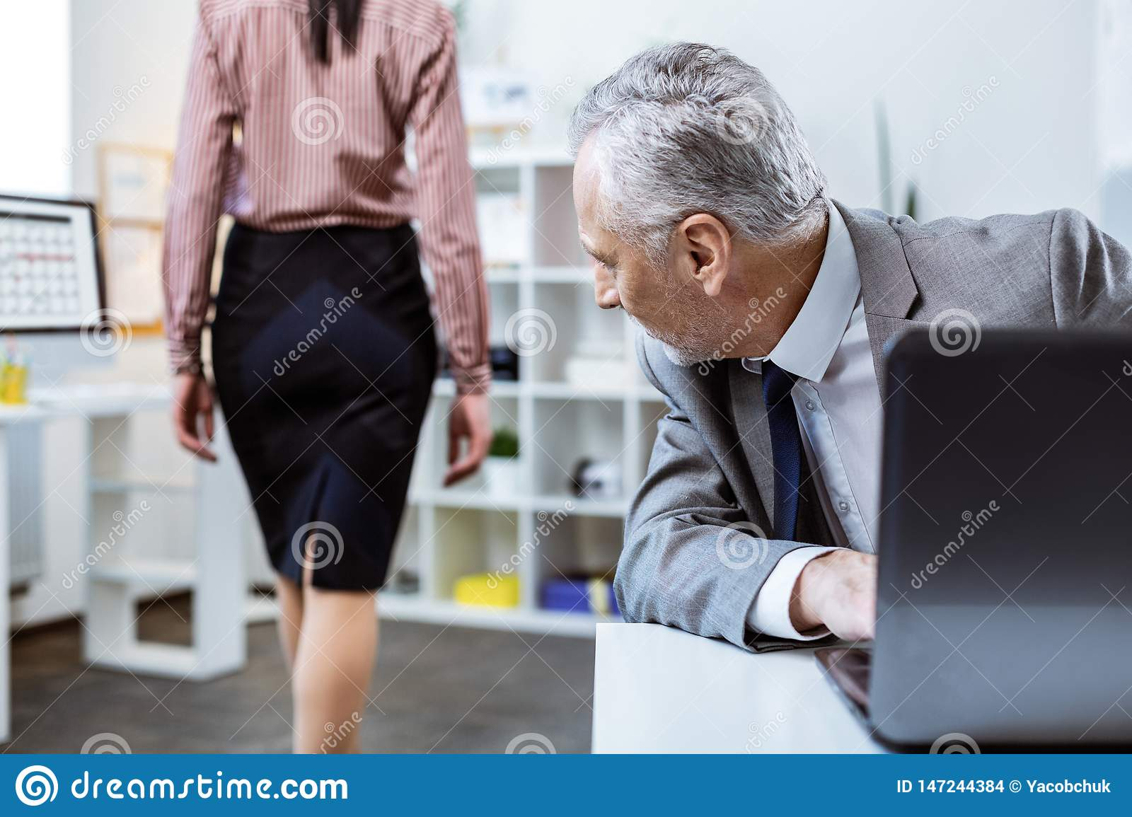 Inappropriate senior worker actively turning around while female colleague