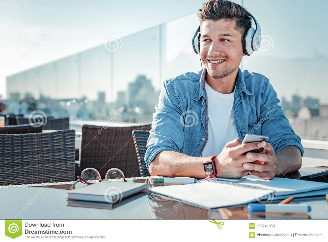 Beaming young man sitting on terrace and listening to music
