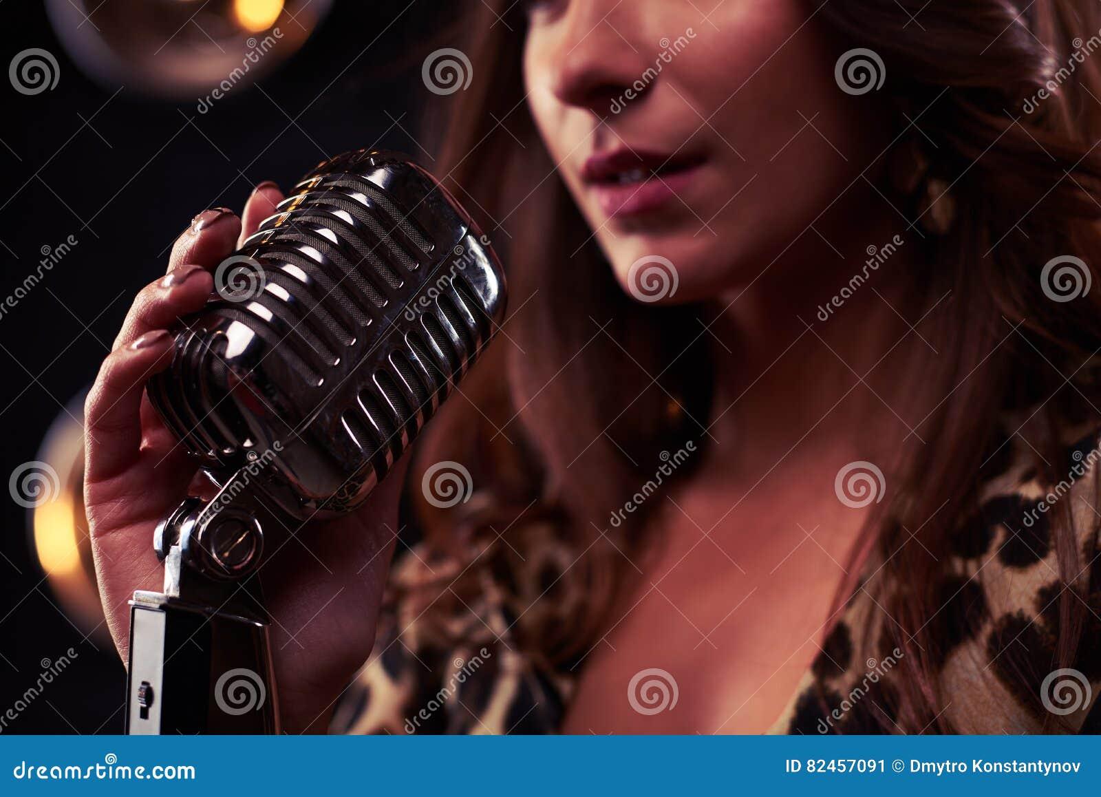 Beanspruchen Sie Fokus eines Mädchens stark, das ein silbernes Weinlesemikrofon hält