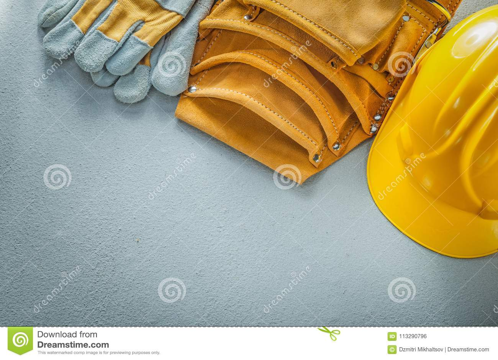 Bearbeiten Sie die Schutzhandschuhe des Gurtes, die Sturzhelm auf konkretem backgrou errichten