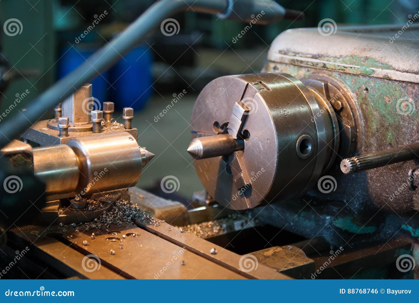 Bearbeta med maskin detaljen på metalldrejbänken