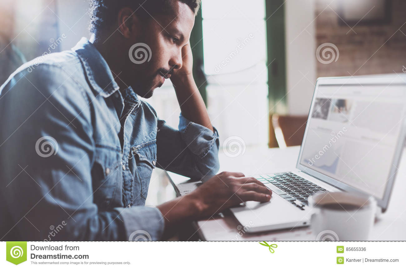 Bearded African man working on laptop while spending time at home.Concept of young business people using mobile devices