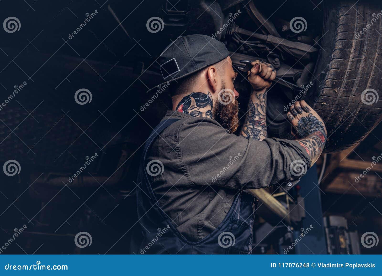 Bearded Auto Mechanic In A Uniform Repair The Car`s