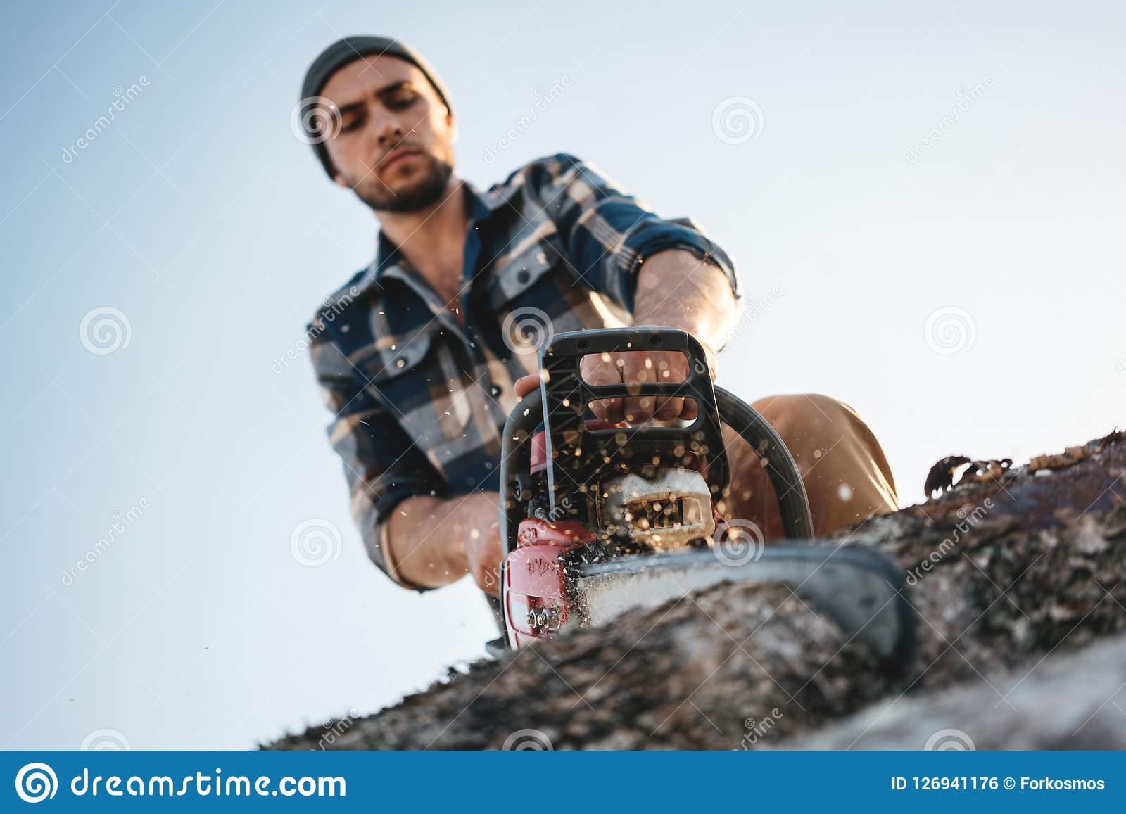 Bearded brutal lumberjack wearing plaid shirt sawing tree with chainsaw for work on sawmill