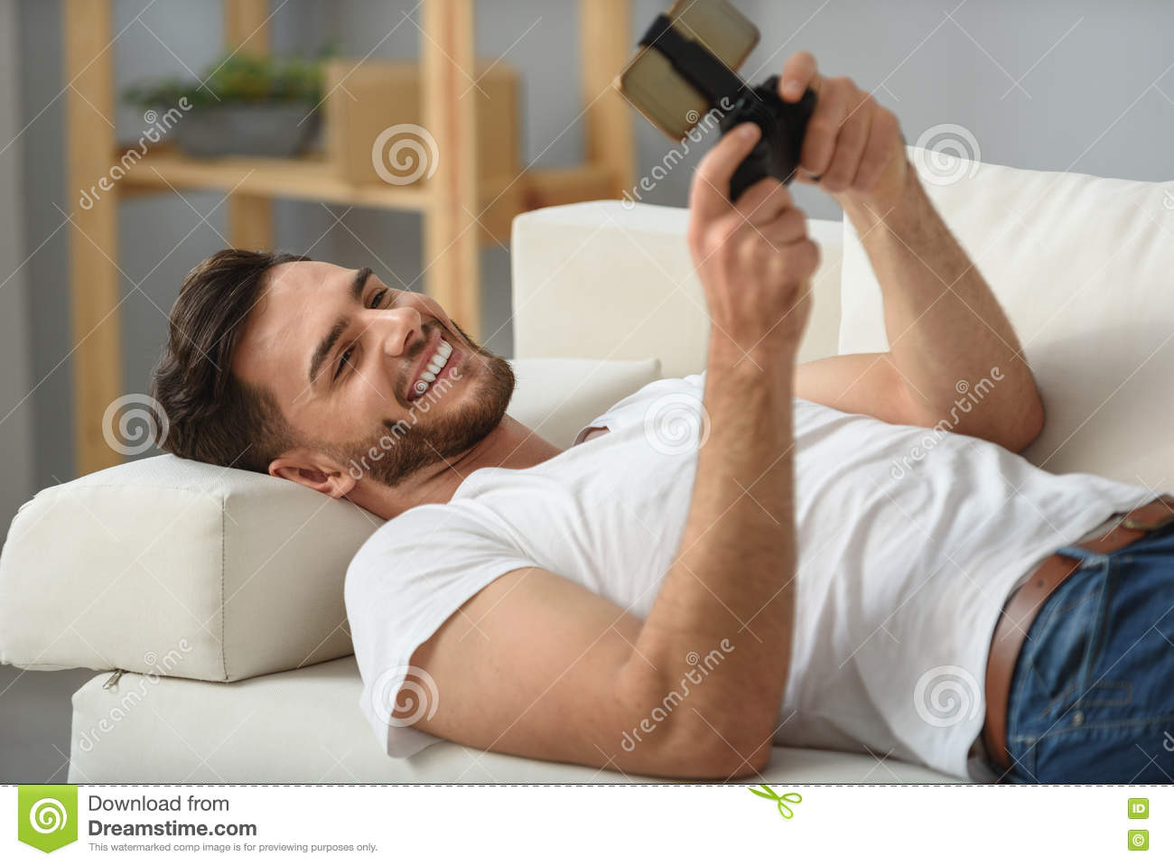 Bearded Guy Lying With Phone On A Couch Stock Photo - Image: 78946505