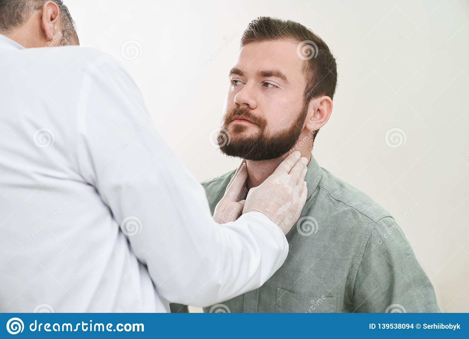 Bearded handsome man having neck and lymph nodes checked.