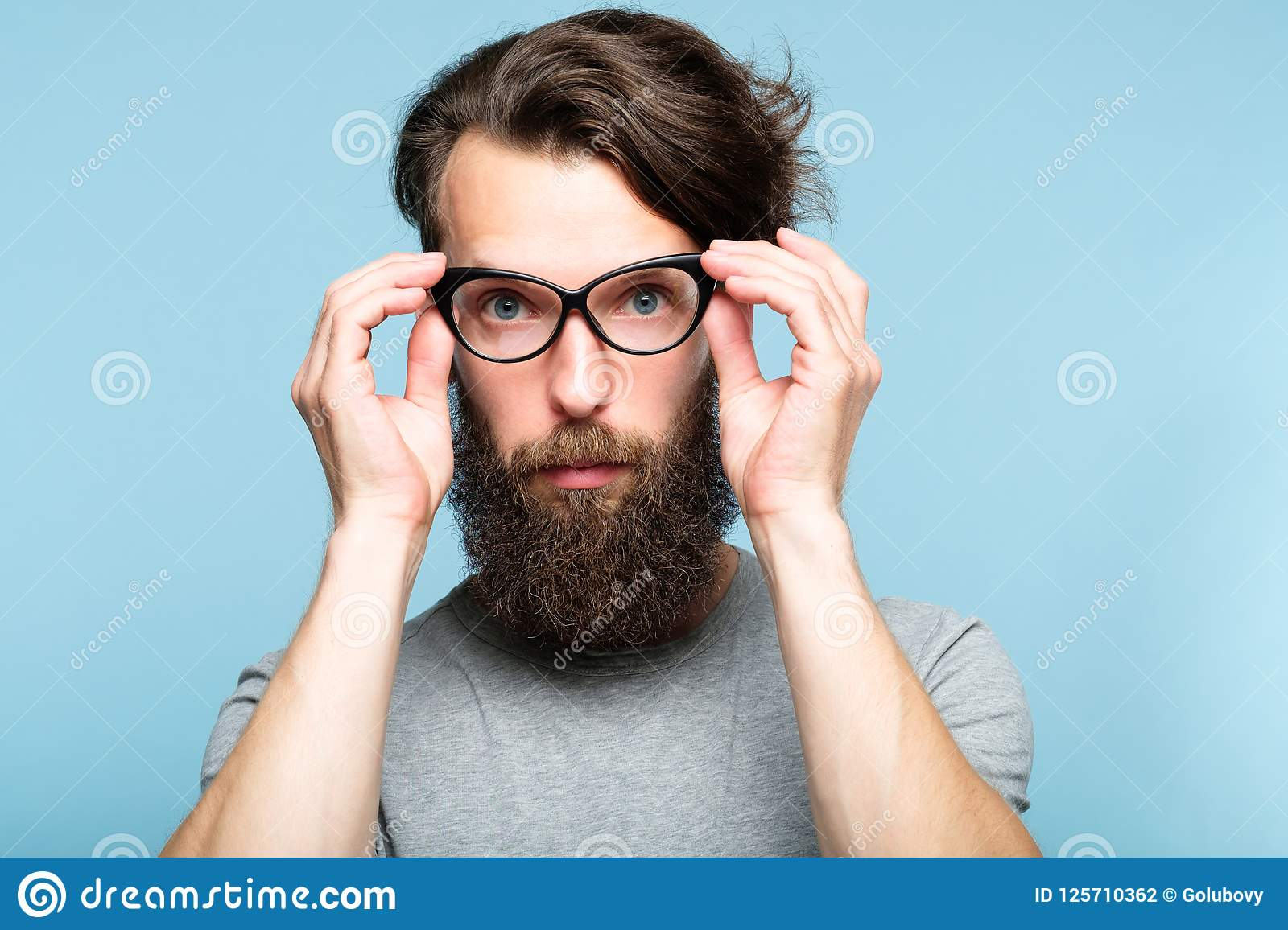 9f876f5ba102 Bearded hipster guy fixing his cat eye glasses. stylish modern fashionist.  portrait of a geeky quirky eccentric man on blue background.
