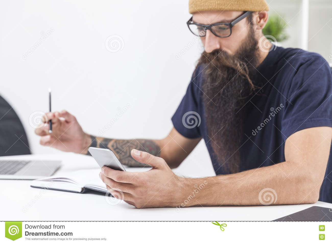 Bearded hipster is looking at his mobile