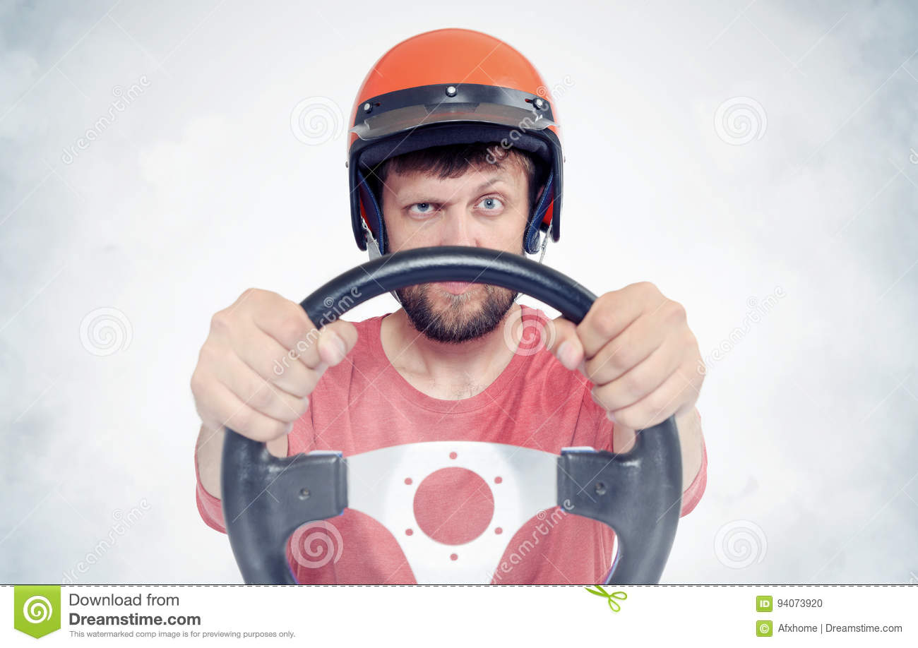 Bearded male in red helmet with steering wheel. car driver concept