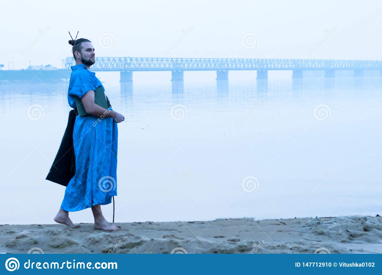 Bearded man in blue kimono with book on river bank