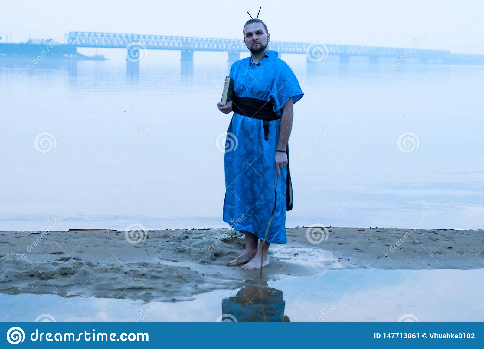 Bearded man in blue kimono holding book on river bank in fog and looking at camera
