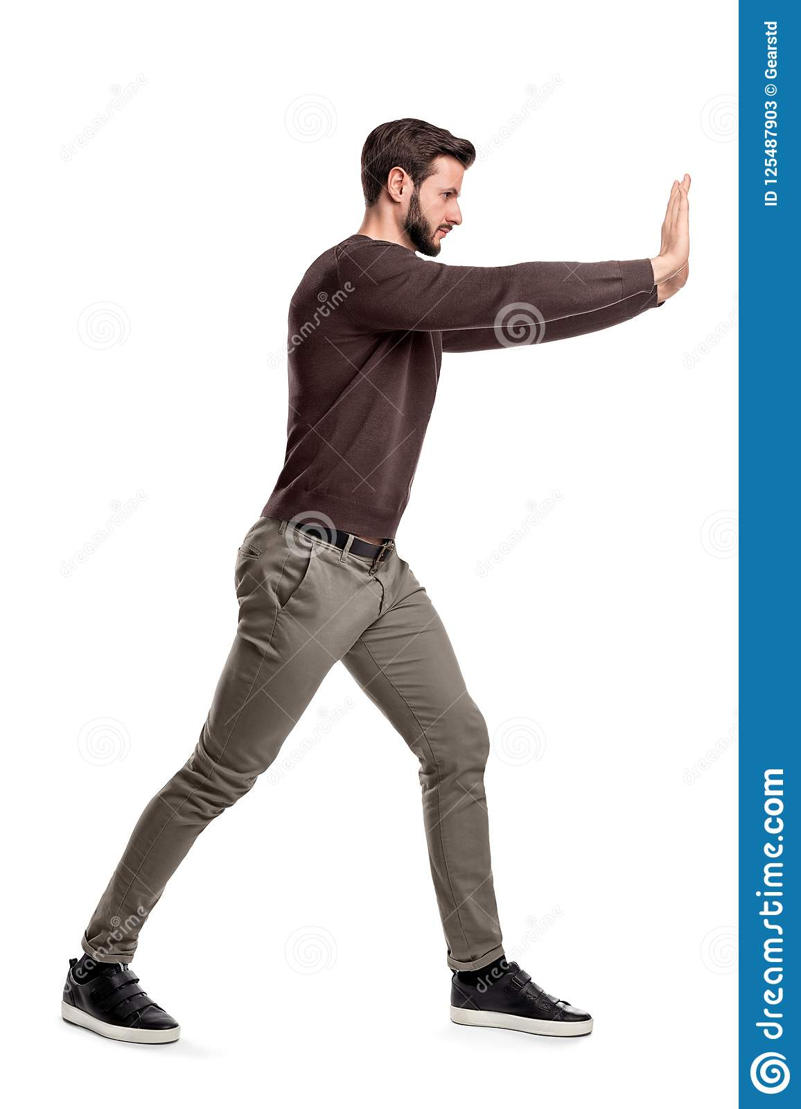 A bearded man in casual clothes tries to push a heavy object with both arms with one leg put in front for balance.
