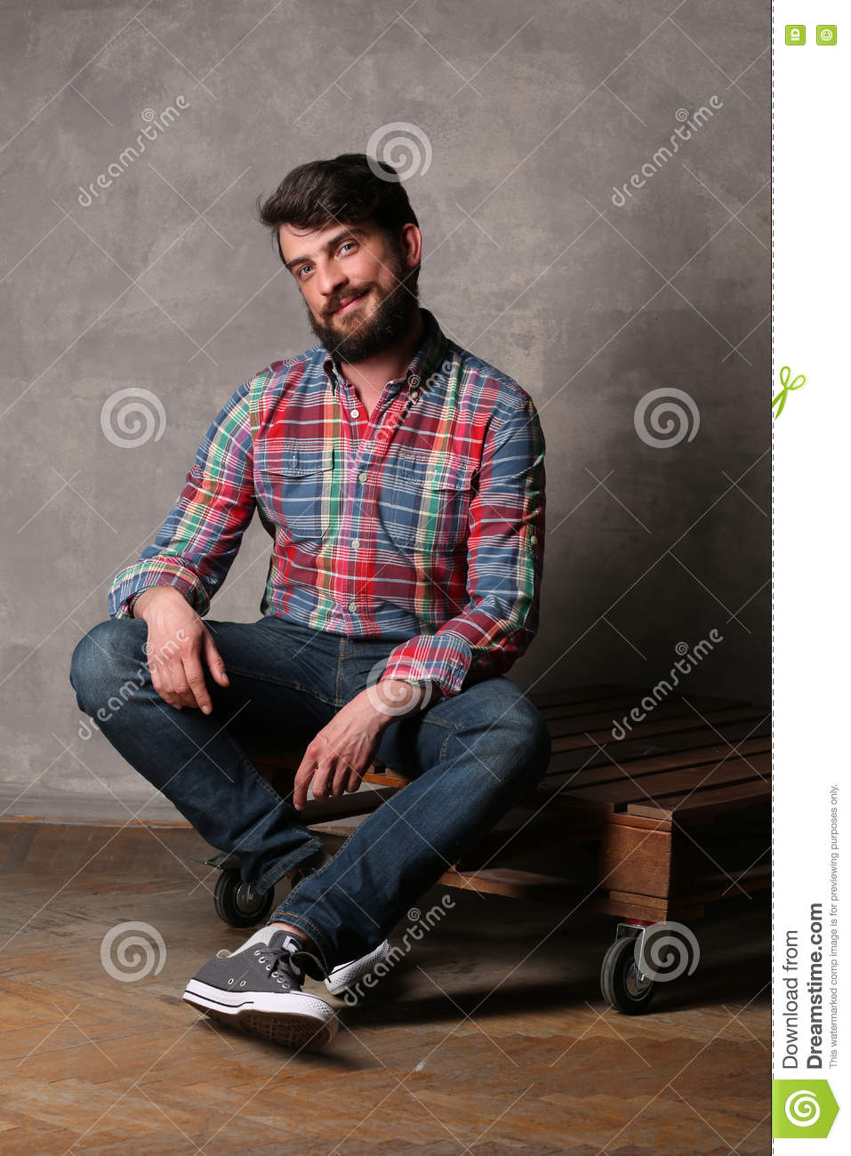 f2c7ce0198 Bearded Man In Colorful Shirt And Jeans Sitting On A Deck Stock ...