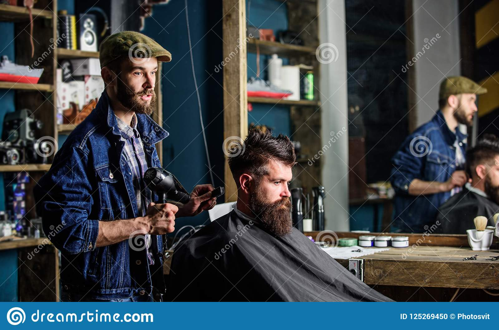 Bearded man getting groomed at hairdresser with hair dryer while sitting in chair at barbershop. Hipster concept