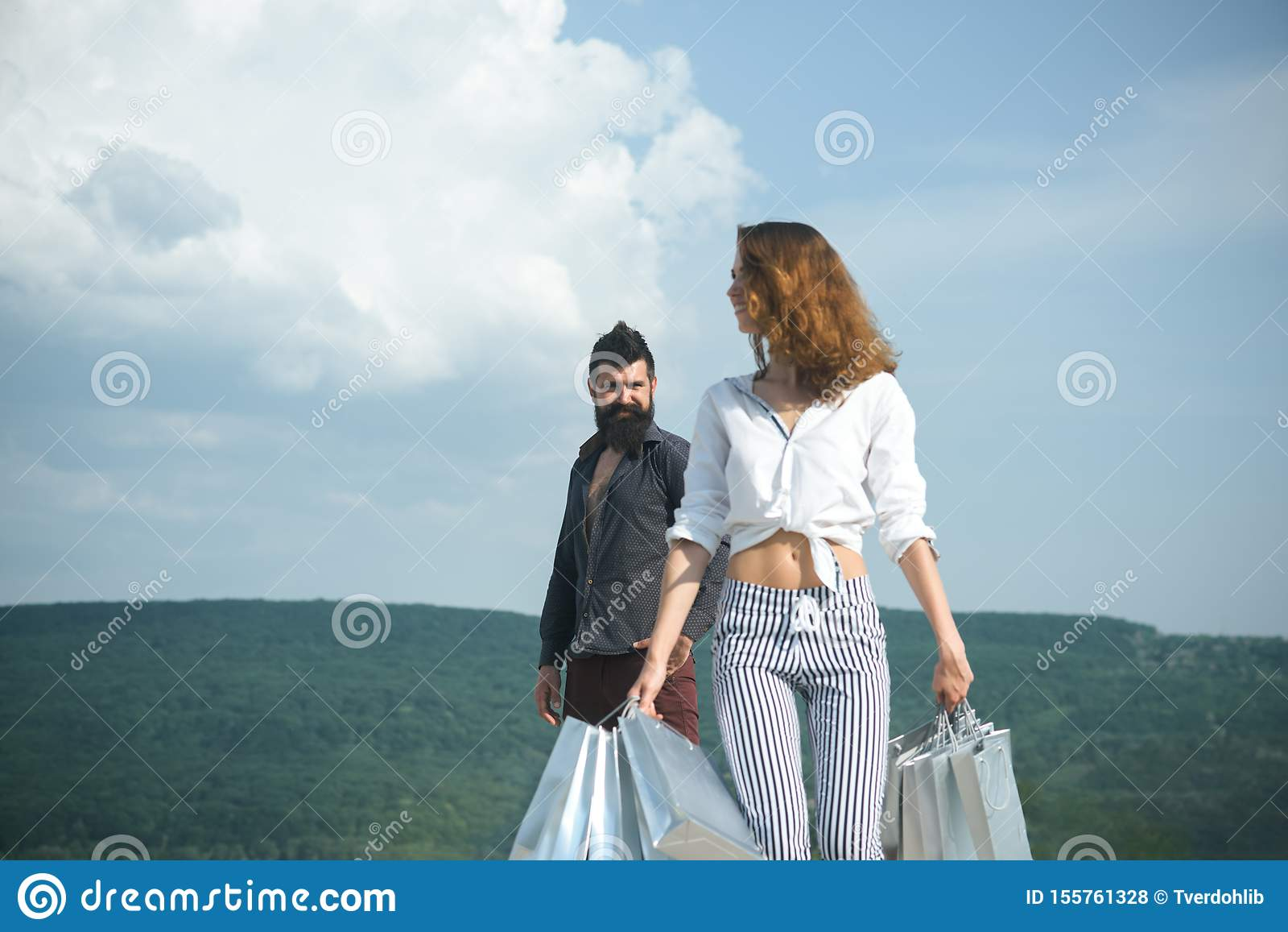 Bearded man with happy woman hold shopping bag. successful shopping. sense of freedom. couple in love. present packages