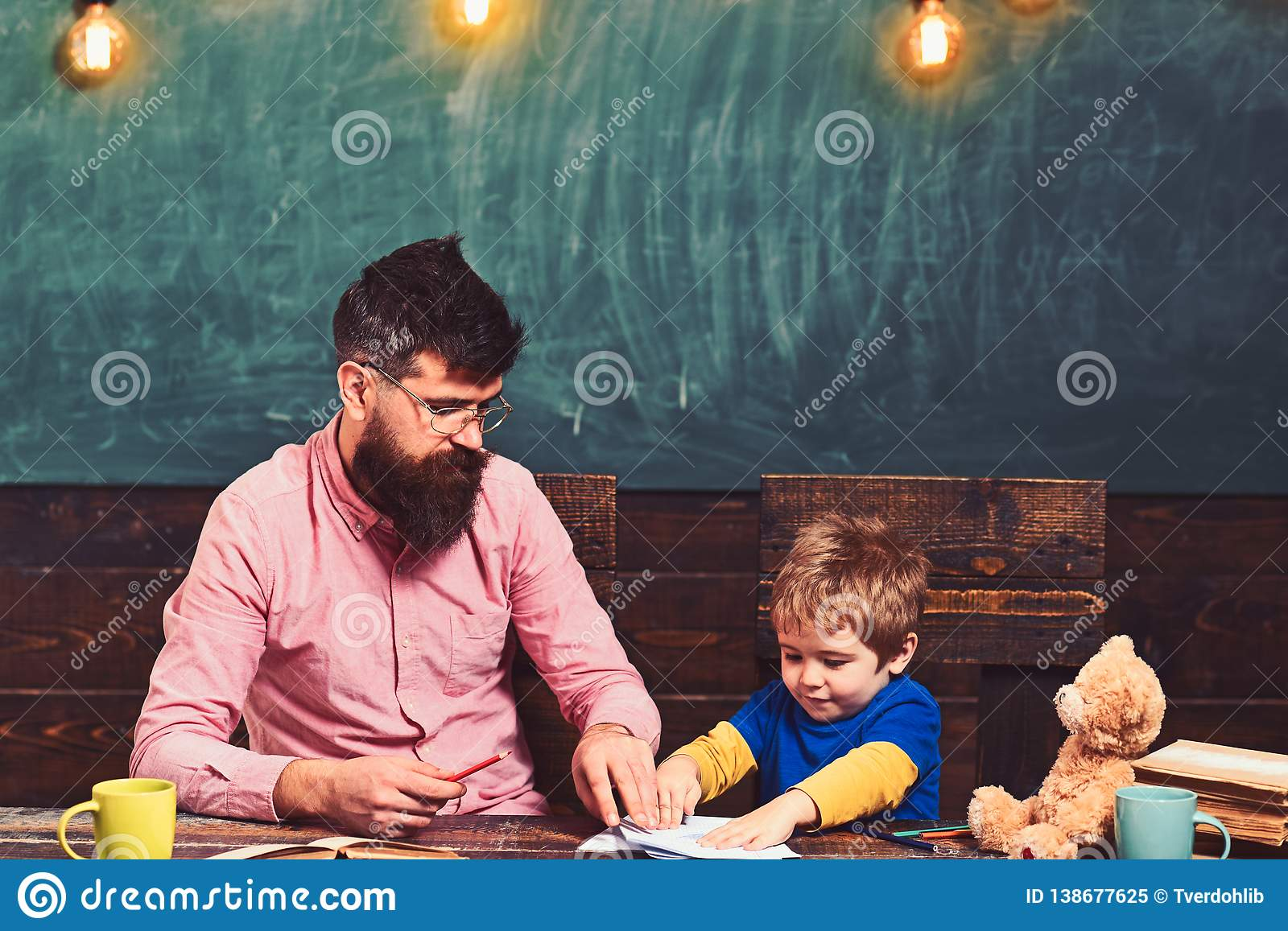Teacher and little kid sitting at desk with books and teddy bear. Schoolboy playing with copybook. Strict teacher in