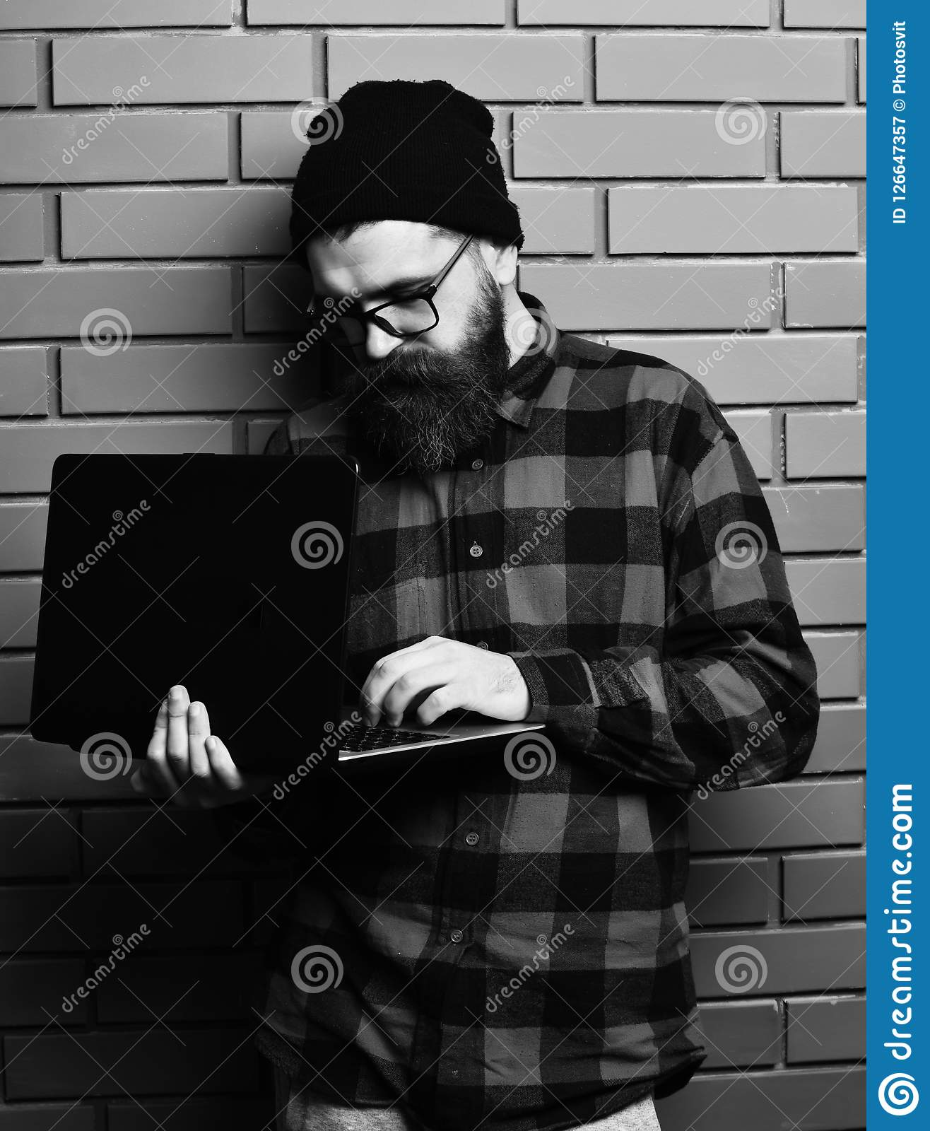 Bearded man, long beard. Brutal caucasian serious unshaven hipster holding laptop in red black checkered shirt with hat
