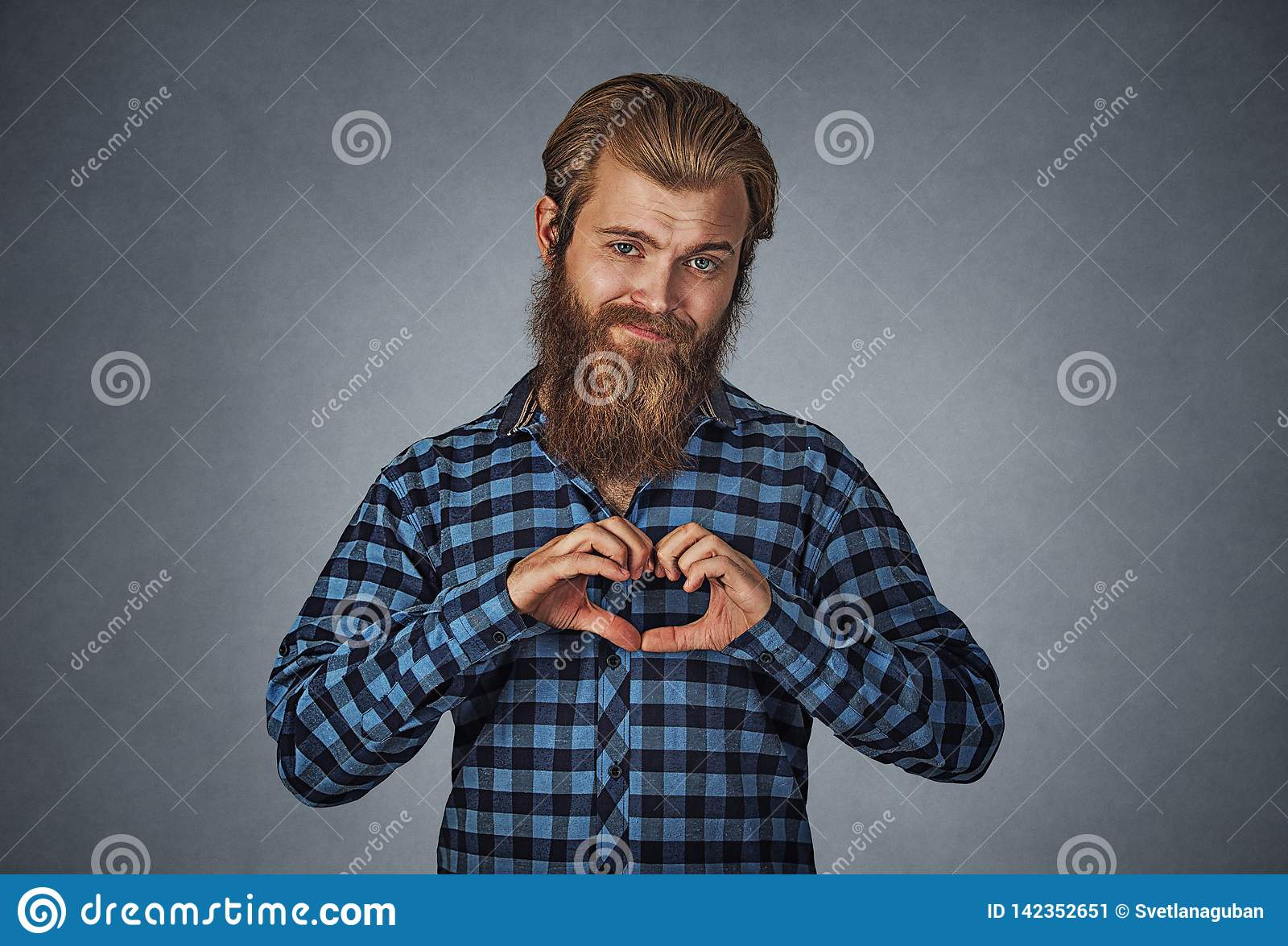 Bearded man making heart gesture with fingers