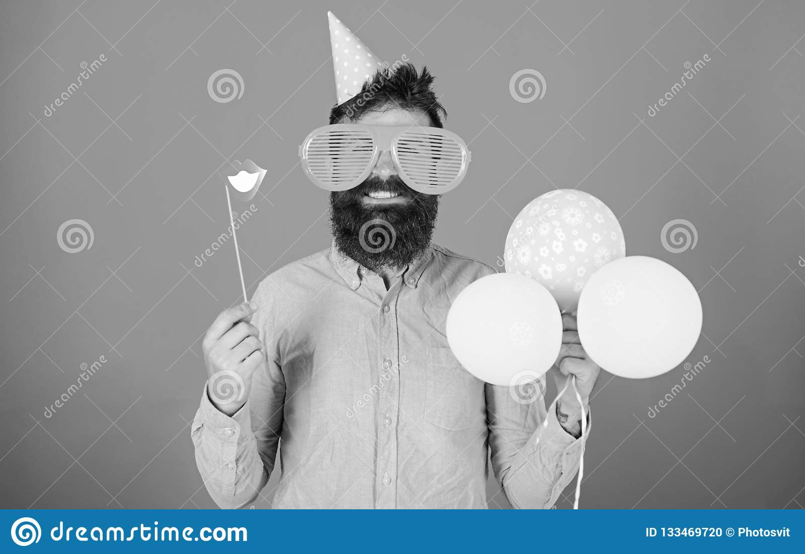 Bearded man with party accessories, surprise concept. Man with paper lips, enormous crazy glasses and balloons isolated