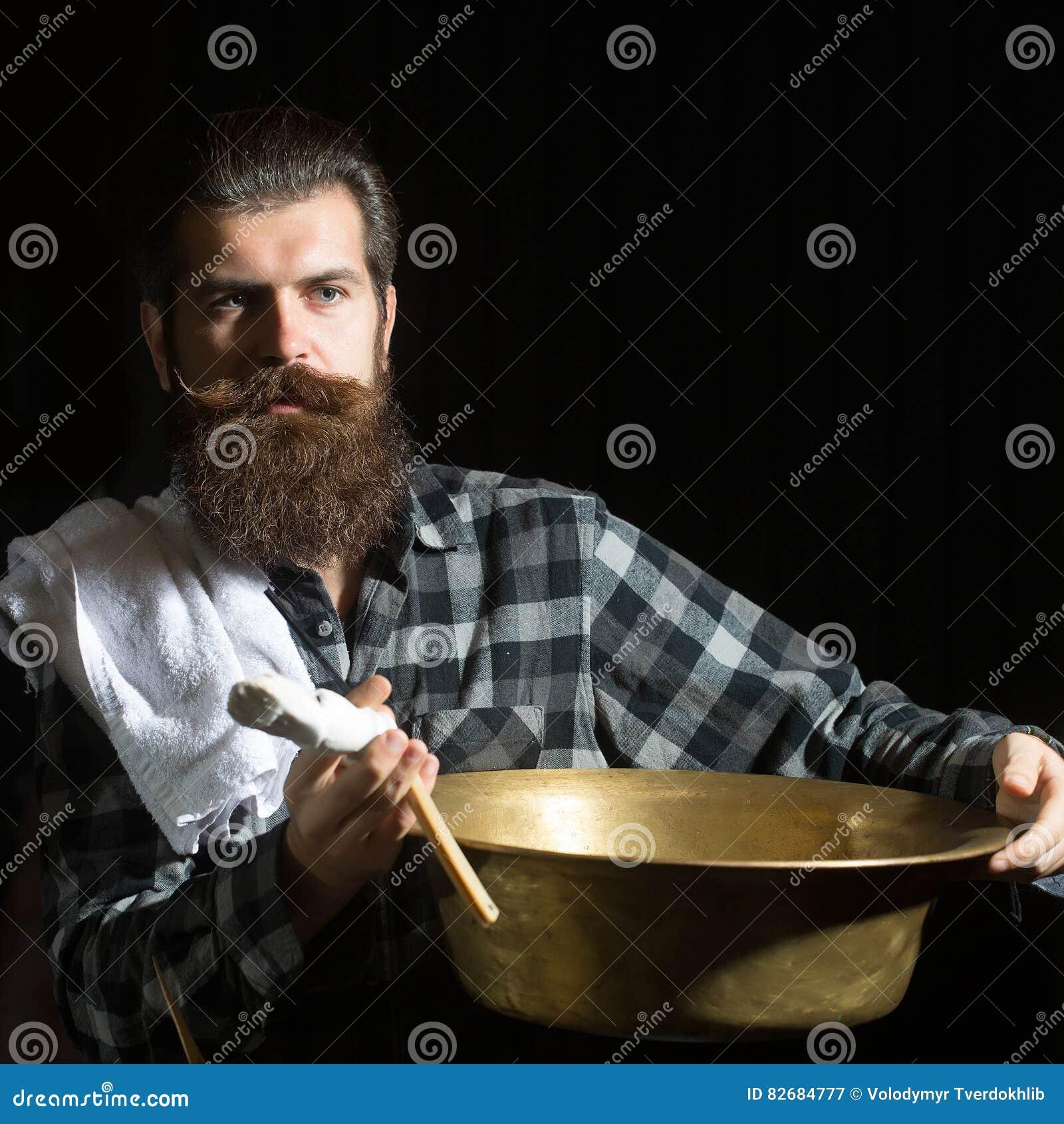 Bearded man shaves with razor