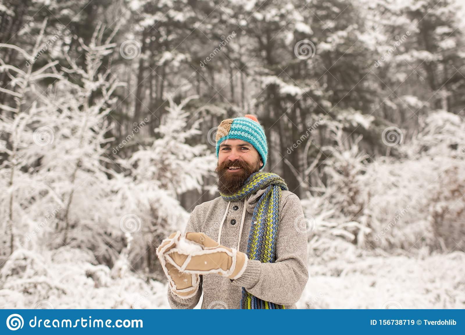 Bearded man smile with snowball in snowy forest