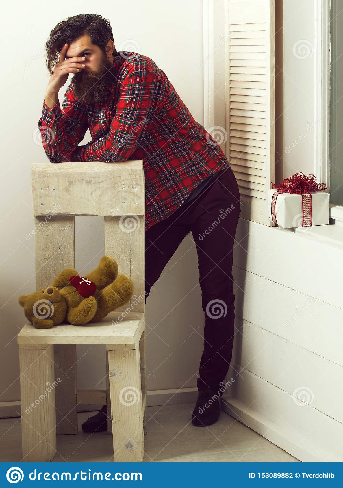 Bearded man standing at chair with teddy bear