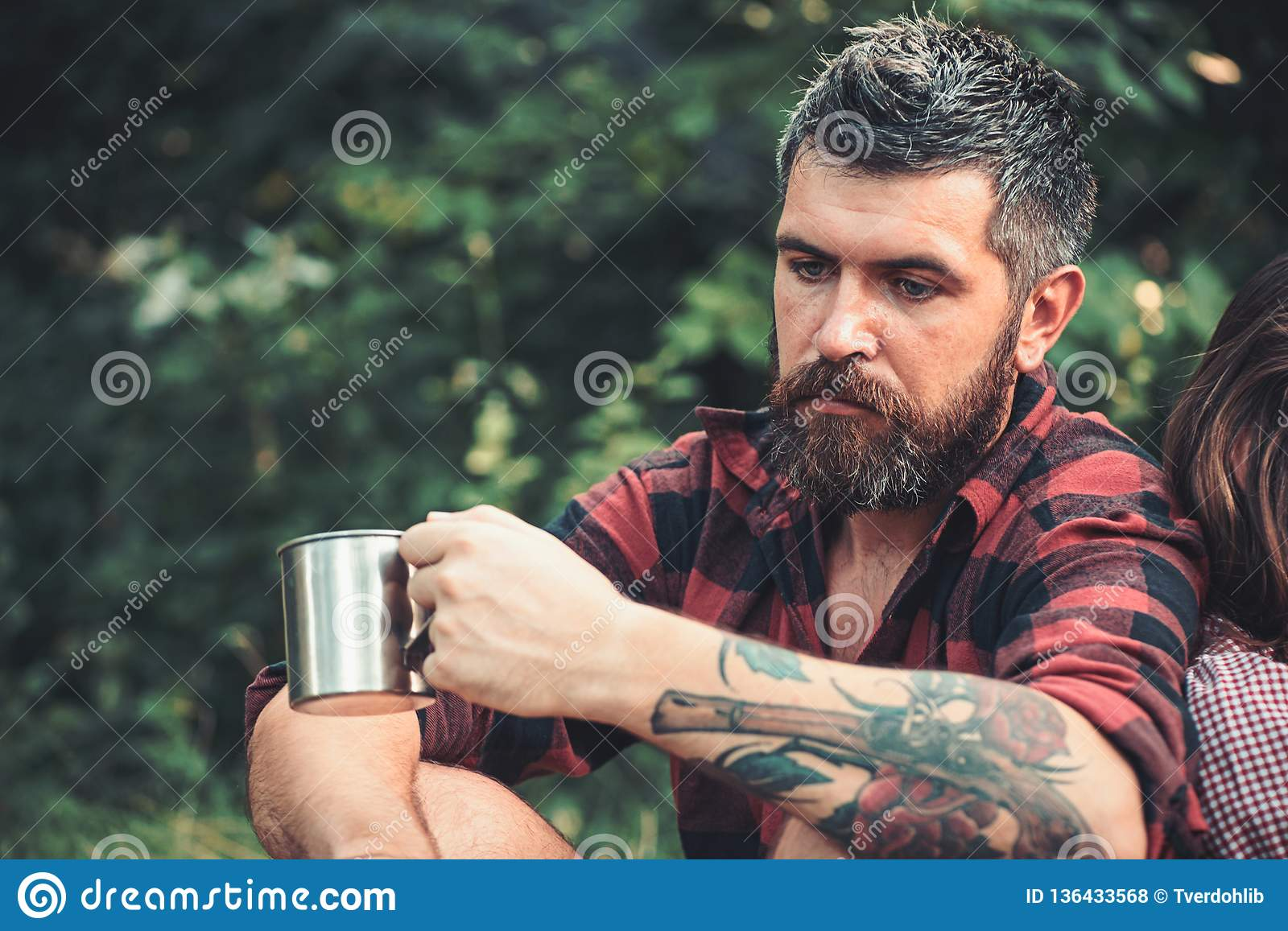 Bearded man with tea or coffee cup in forest. Tourist in plaid shirt hold mug. Hipster with long beard relax on natural