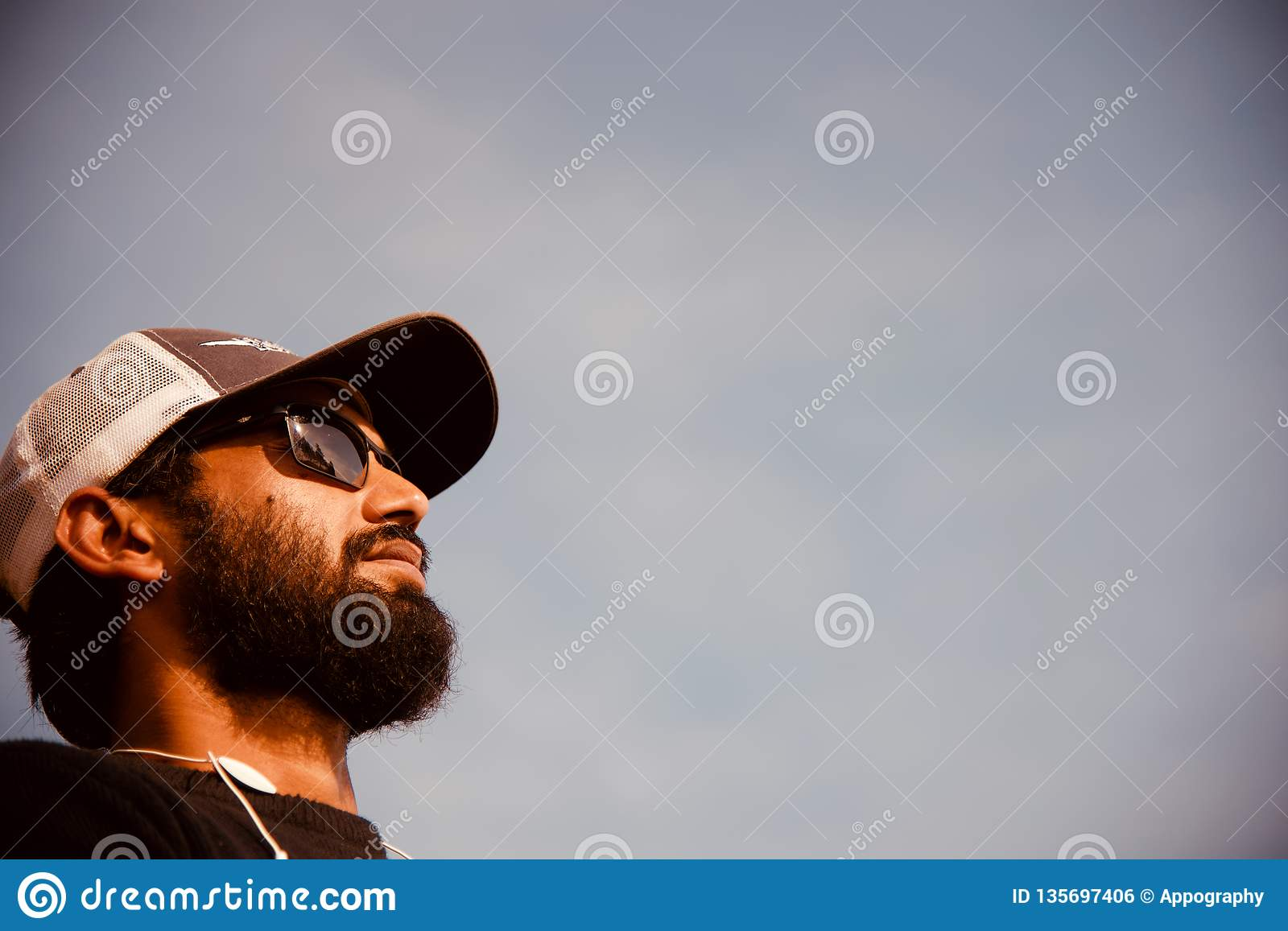 A bearded man wearing cap and sunglasses standing in a place