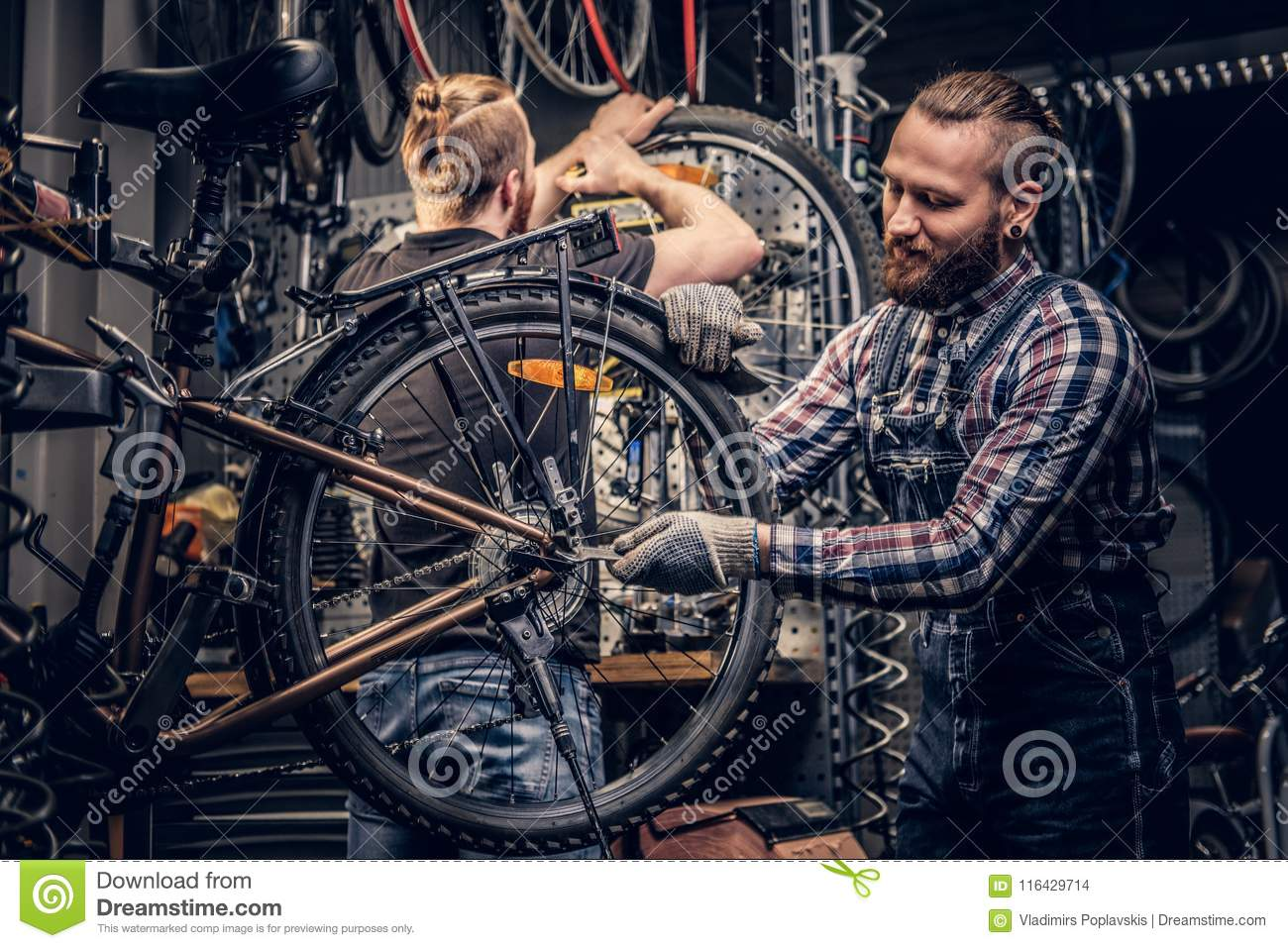 Mechanic doing bicycle wheel service manual in a workshop.
