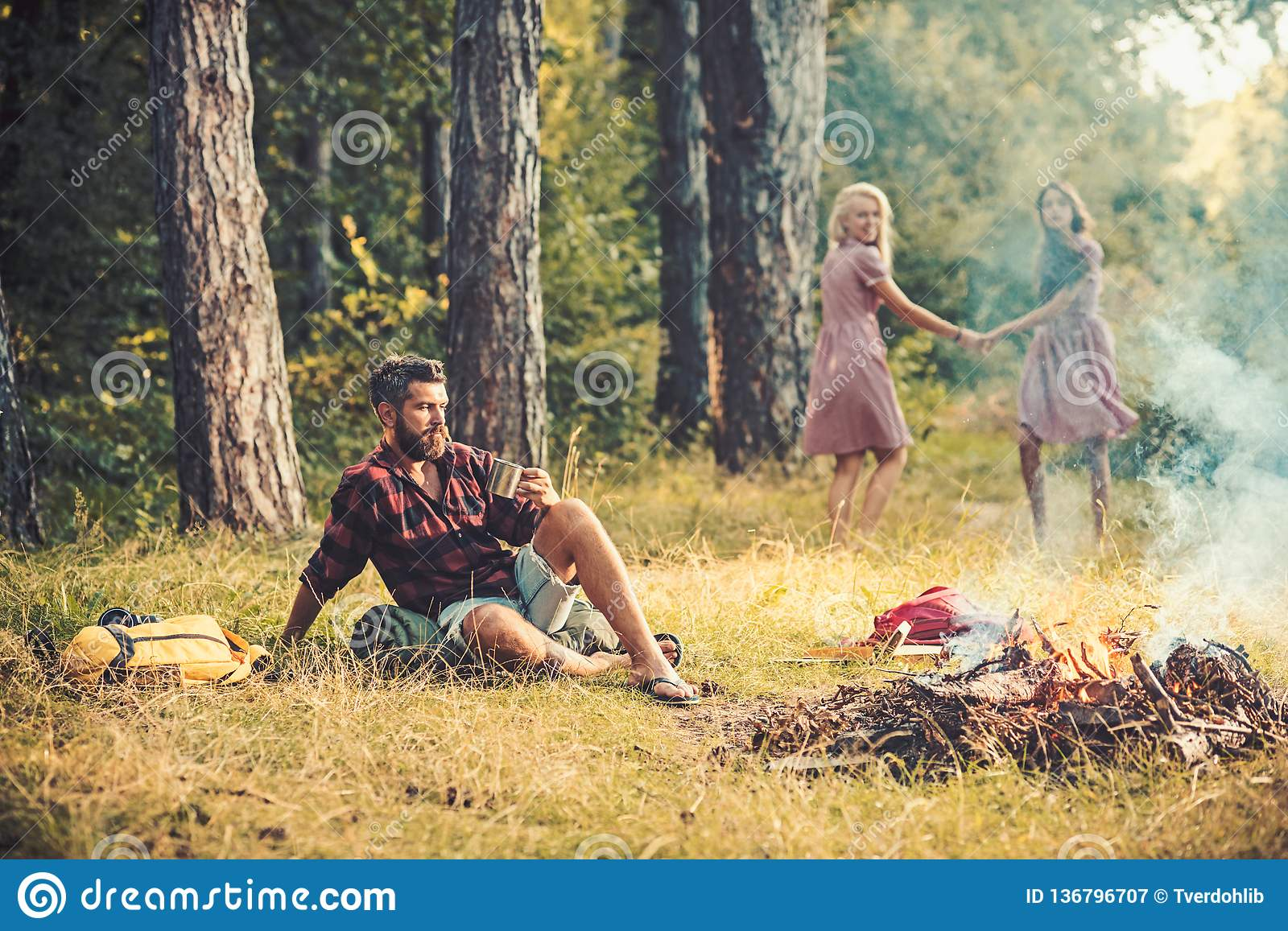 Bearded man drink tea or coffee at bonfire with women on blurred background. Bearded man sit at campfire