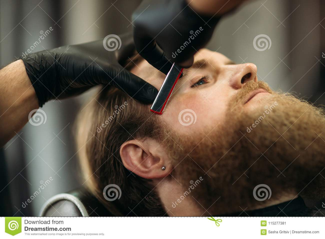 Bearded man with long beard getting stylish hair shaving , haircut , with razor by barber in barbershop