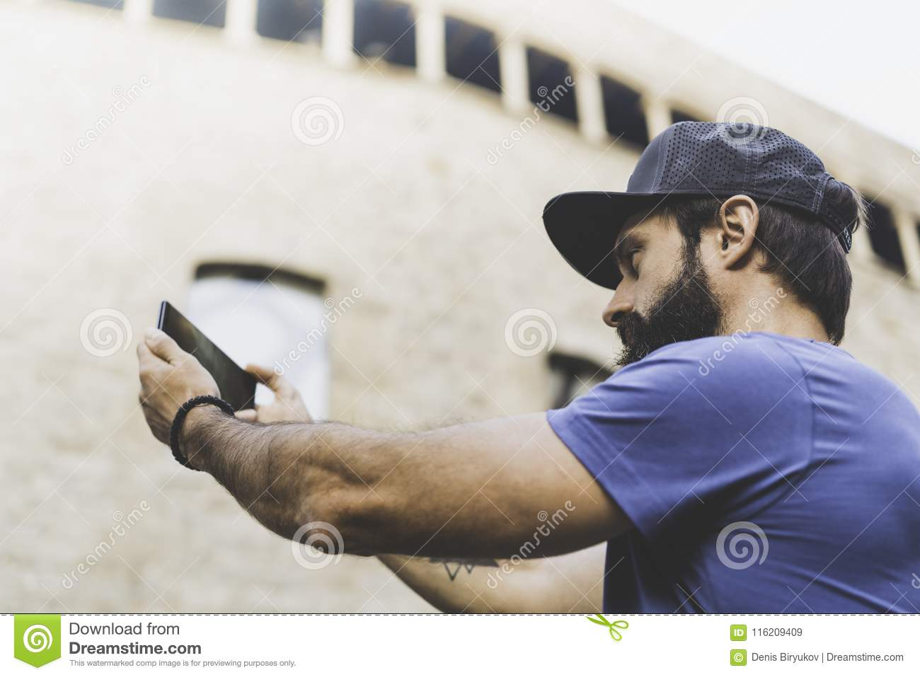 5a8041abc5d Bearded muscular man wearing black snapback cap and making selfie with his  own smartphone. Man walking on street and using mobile.Blurred background.