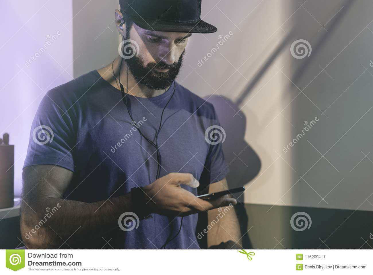 819eb32370d Bearded muscular man wearing black snapback cap standing on cafe with  headphones. Men using mobile