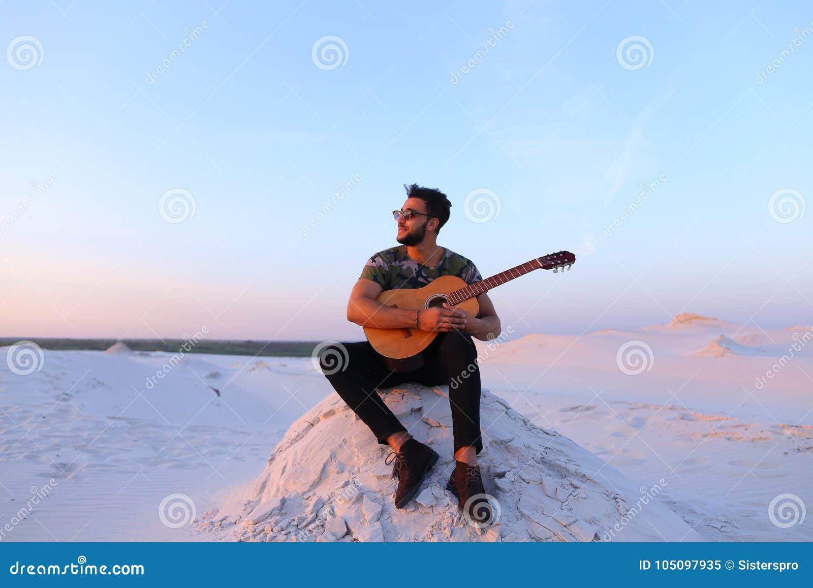 Attractive Arabian Guy Sings Songs On Guitar Sitting On Hill In