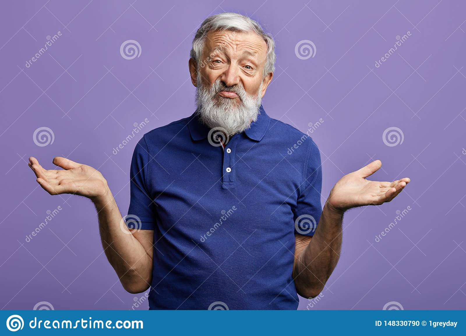 Bearded old man expresses clueless with raised arms looking at the camera