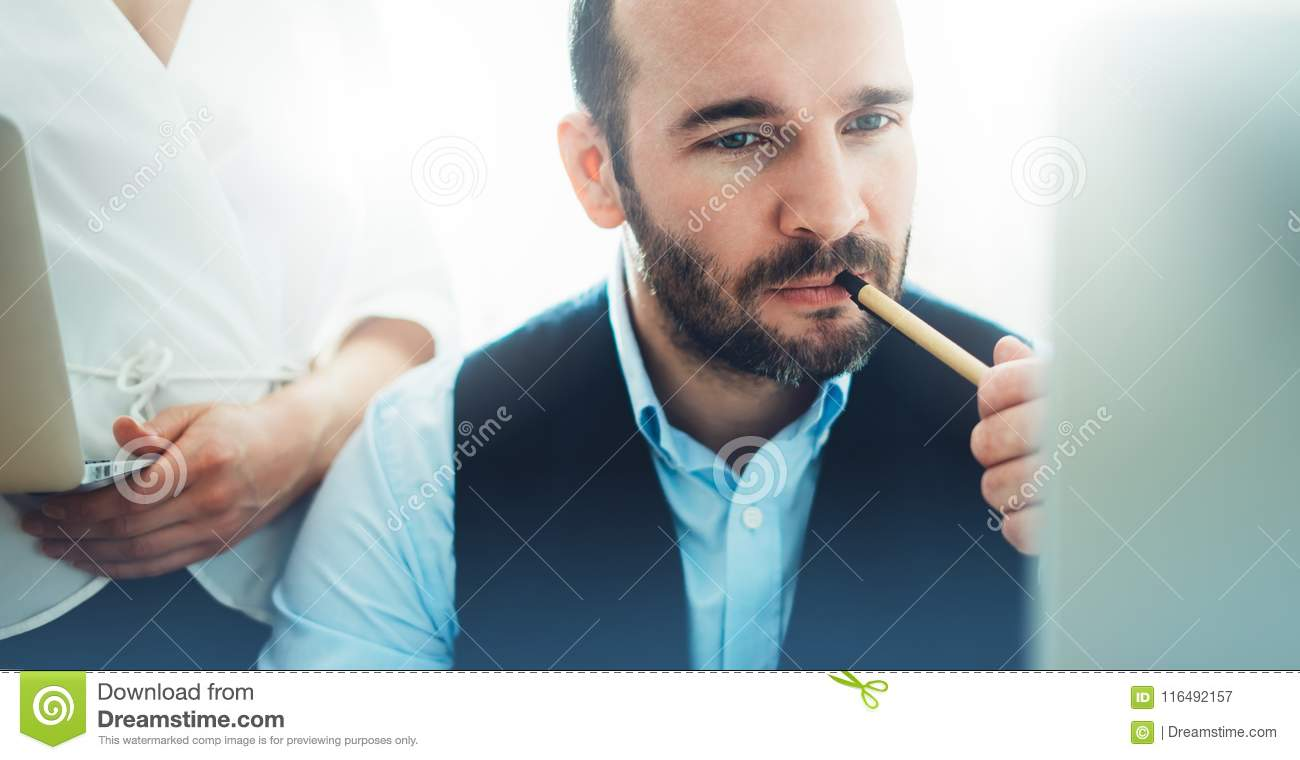 Bearded young businessman working on modern office. Consultant man thinking looking in monitor computer. Manager coworking on work